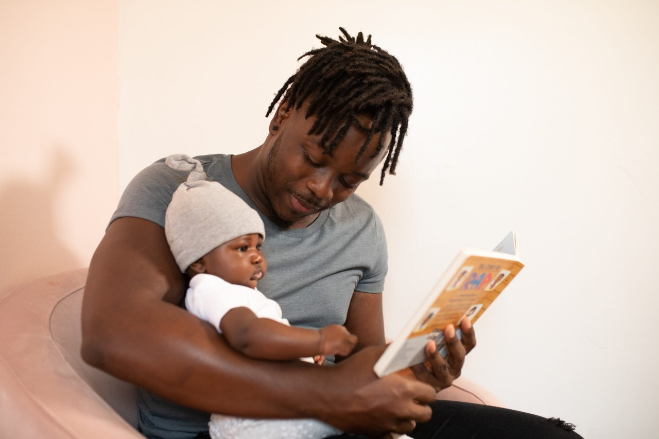 Man in Grey Shirt Reading With Toddler